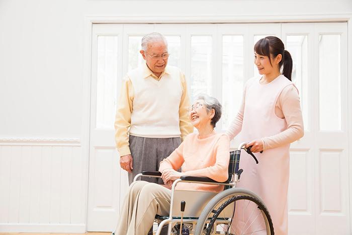 車椅子の女性と老齢の男性とエプロン姿の女性