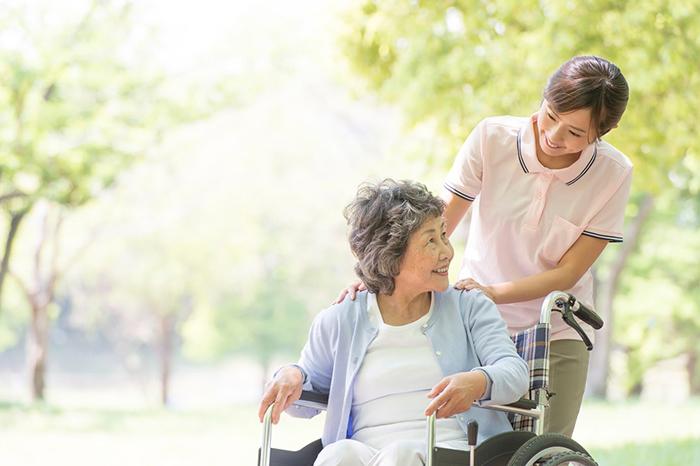 車椅子の女性の肩に手を置く女性